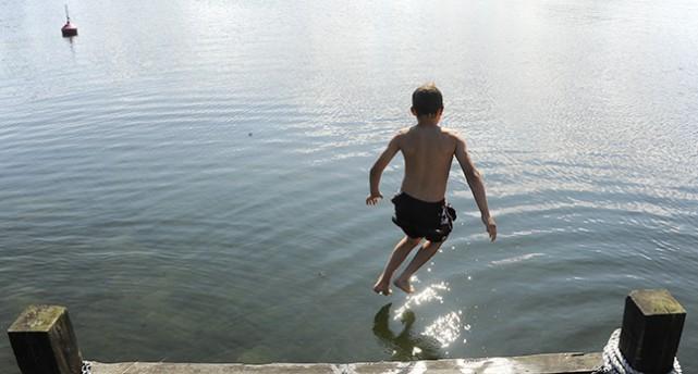 Pojke hoppar från brygga.
