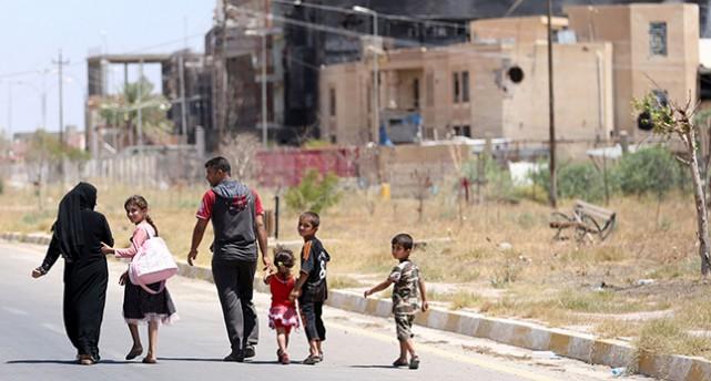 En familj utanför förstörda hus