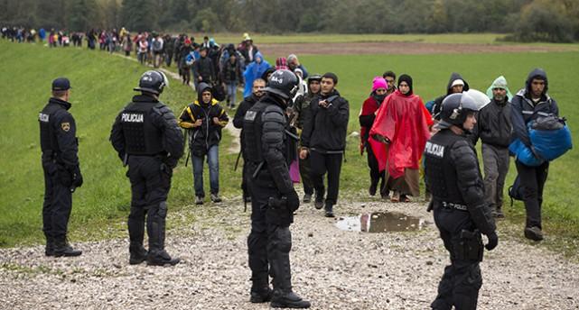 En rad med flyktingar går över ett fält