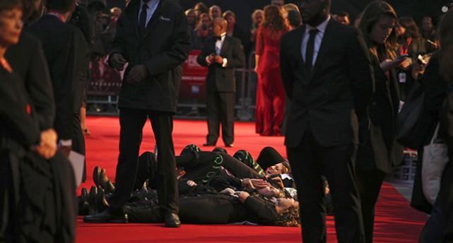 människor ligger ner på röda mattan.