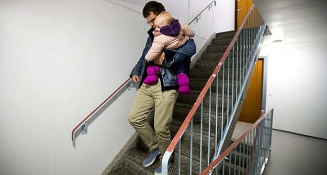 En pappa bär sitt barn nerför en trappa.