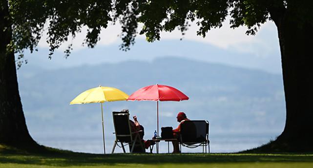 Två personser sitter under parasoller.