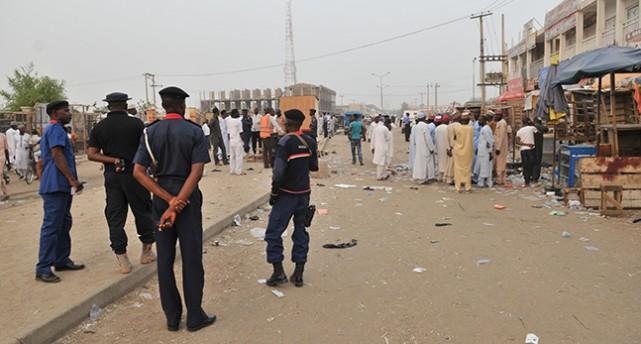 Poliser står och tittar på människor på väg till marknaden
