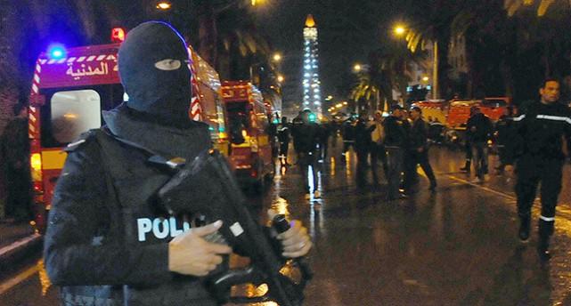 En maskerad polis med vapen vaktar en gata