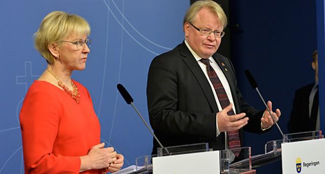 Två ministrar i varsin talarstol.