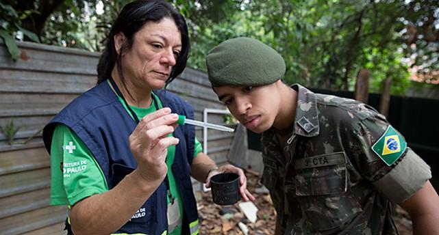 En forskare och en soldat tittar på en larv från den farliga myggan i Sao Paulo i Brasilien.