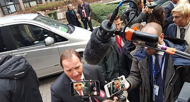 Stefan Löfven går mellan journalister med mikrofoner.