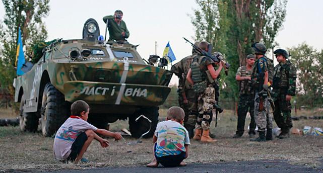 Barn sitter nära en stridsvagn och några soldater