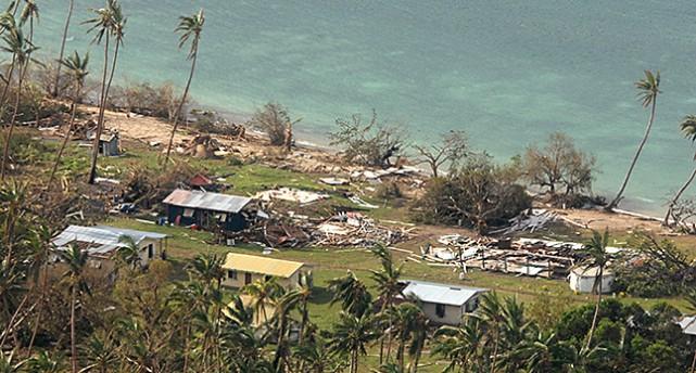 En bit av en strand med skadade hus på Fiji.