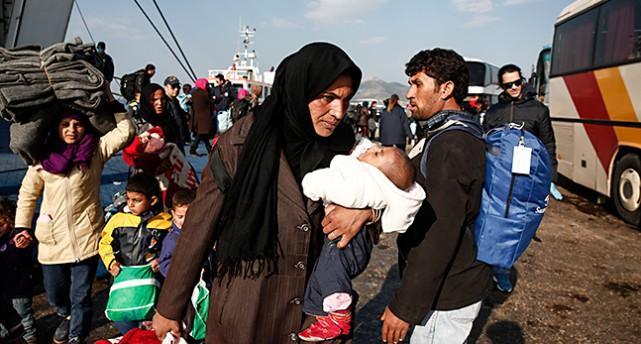 En kvinna på flykt som bär på sitt barn i Grekland.