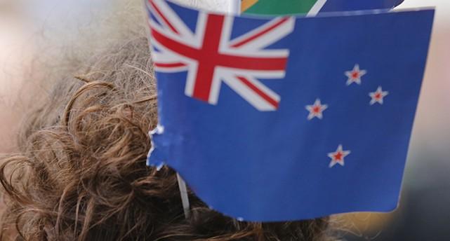 Nya Zeelands flagga. Flaggan är blå med röda stjärnor. I hörnet finns en liten miniatyr av Storbritanniens flagga.