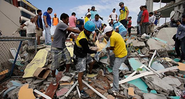 Människor hjälper en överlevande vid ett rasat hus.