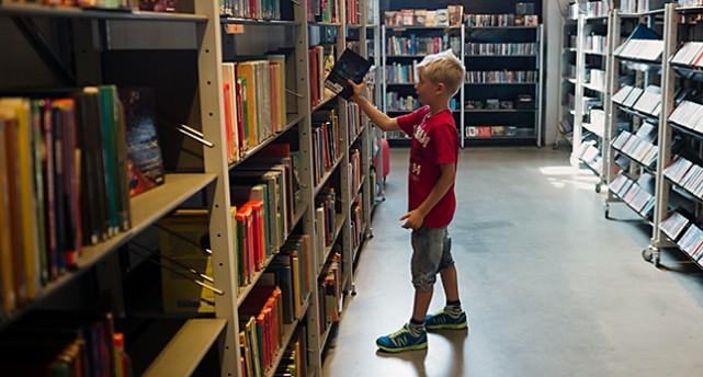 Ett barn står vid en lång bokhylla med böcker på ett bibliotek. Hen drar ut en bok.