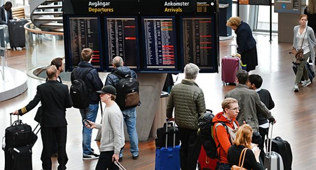 Flera personer med resväskor står framför avgångs och ankomsttavlorna.