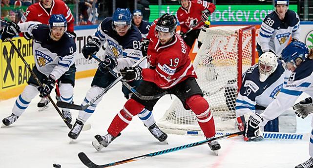 Två spelare från Kanada respektive Finland slåss om pucken vid Finlands målbur.