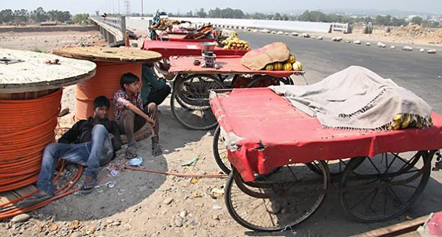 En torr och dammig gata. Flera nästan tomma bord med hjul står längs gatan. Man ser personer som hukar sig i skuggan under ett par bord.