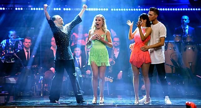 Elisa i grön klänning står i mitten och har just vunnit. BIanca till höger i rött applåderar. Hennes danspartner i vit tröja håller om henne. Elisas danspartner till vänster i svart sträcker händerna i luften.