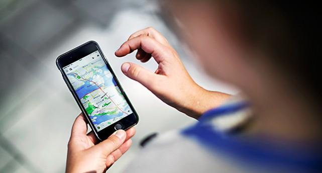 En person håller i en mobil. Man ser en karta på mobilen och personens två händer.