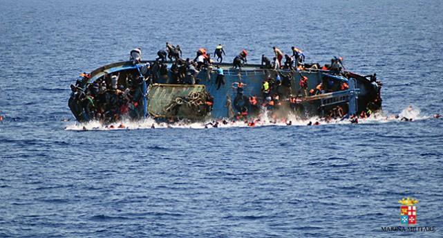 En fullt lastad båt har vält på havet. Människor har hoppat i havet, några hänger kvar i den kantrade båten.