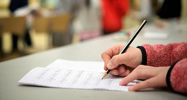 ett barn skriver på ett papper med en penna.