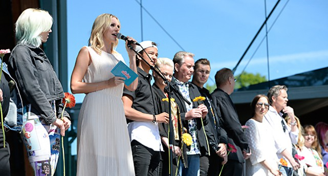 Sanna Nielsen pratar i en mikrofon bredvid några artister.