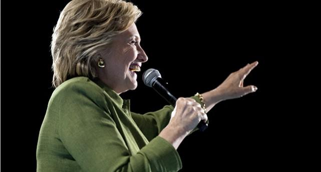 Hillary Clinton i halvfigur och i profil. Hon håller en mikrofon och ser glad ut.