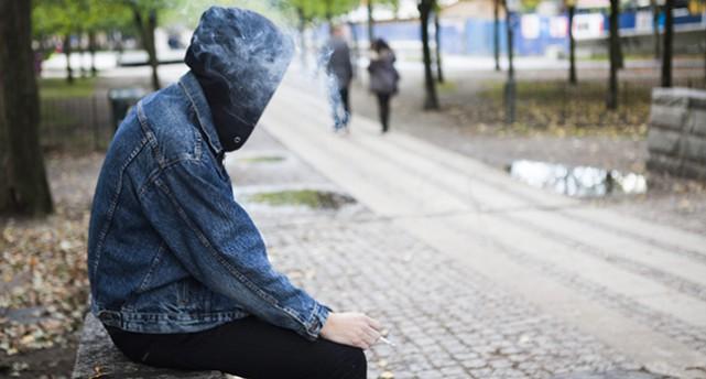 En ung person sitter på en bänk och röker.