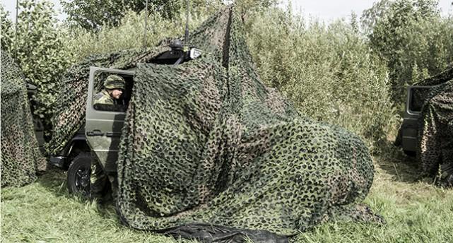Militärer gömmer sig bakom ett grönt skydd ute i naturen.
