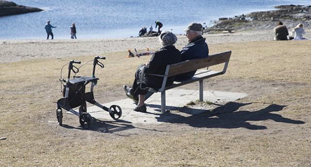 Två äldre personer sitter på en bänk vid en sandstrand och pratar.