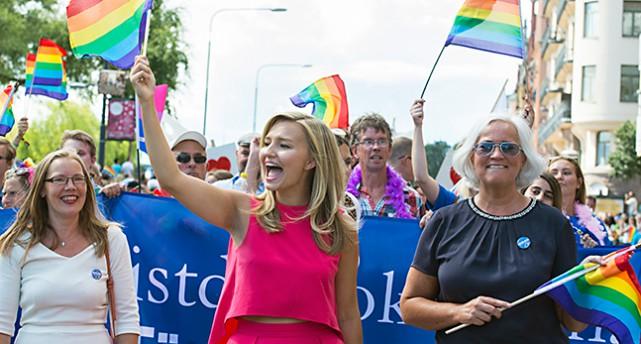 Ebba Busch Thor i en cerise topp viftar med en flagga med regnbågens färger åt människor när hon går i paraden.