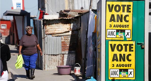 En kåkstad i Sydafrika med plåtskjul. På ett av skjulen finns affischer om valet. En kvinna går förbi.