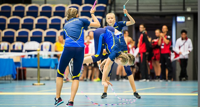 Fyra tjejer i blått och gult som är på golvet i en sporthall. Två snurrar de båda repen, två hoppar mitt i repen. De står på händerna, fast händerna är lyfta från marken mitt i ett hopp.