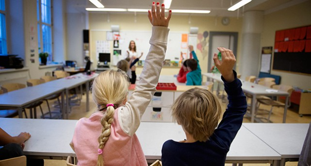 Ett klassrum med barn som räcker upp handen. Man ser barnens ryggar. Längst fram ser man en lärare stå vid whiteboarden.