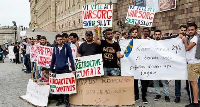Människor håller upp skyltar med budskap om att ändar lagen