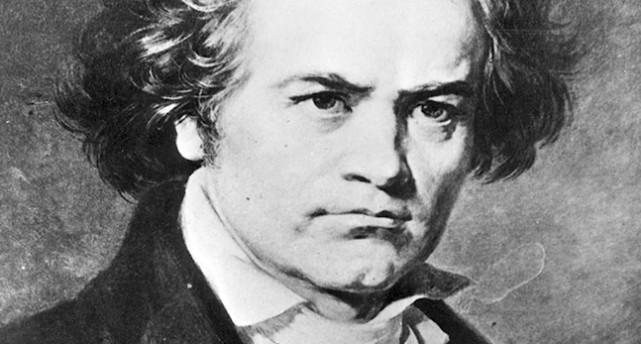 En svartvit bild på Ludwig van Beethoven. Han ser sträng ut. med lätt rynkade ögonbryn och ganska rufsigt hår som hänger ner över öronen. Han har en vit skjorta med krås och en svart kavaj.