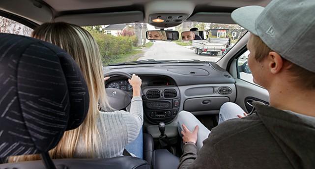 Bild inifrån en bil. En person övningskör och håller hårt i ratten.