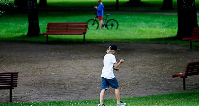 Två personer går med mobiltelefoner på en gräsmatta