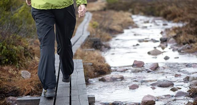 En person vandrar på en vandringsled. En spång längs med ett vattendrag.