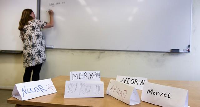 En kateder med namnlappar på elever i förgrunden. Bakom katedern ser man en lärare som skriver på en whiteboard.