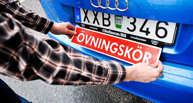 Två armar sätter på en skylt med texten övningskörning på en bil