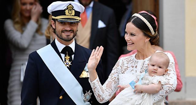 Prins Carl Philip och prinsessan Sofia lämnar kyrkan med sin son Alexander. Carl Philip har uniform. Sofia en vit spetsklänning och hårband av pärlor. Alexander i hennes famn har en vit dopklänning. Sofia vinkar.