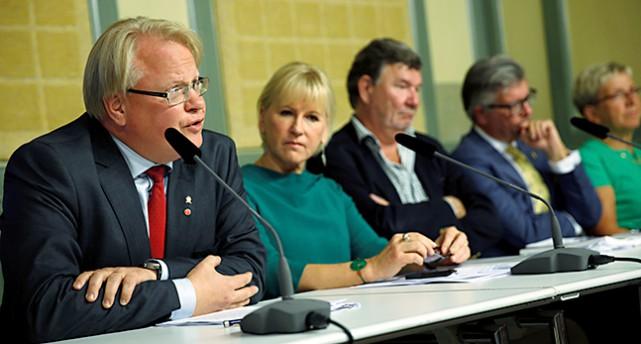 Peter Hultqvist sitter tillsammans med andra politiker vid ett långt bord.