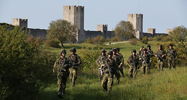 Soldater går bredvid muren i Visby.