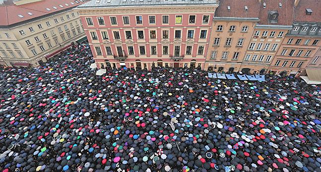 Bilden är tagen uppifrån och visar tusentals paraplyer mellan höga byggnader.