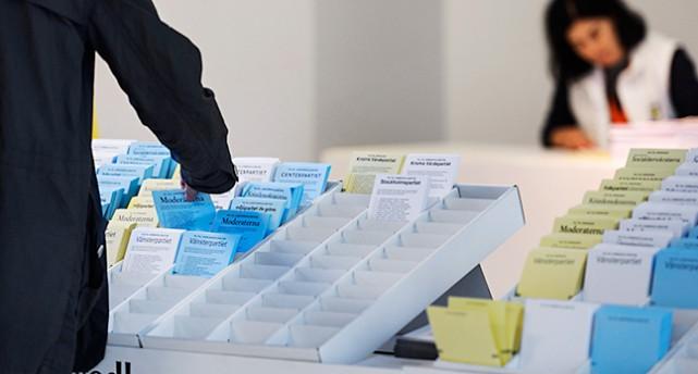 En hand sträcker sig fram för att ta en valsedel.