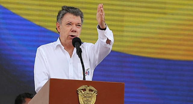 President Juan Manuel Santos står på ett podium och talar. Han har vit skjorta och sträcker ut en arm i luften.