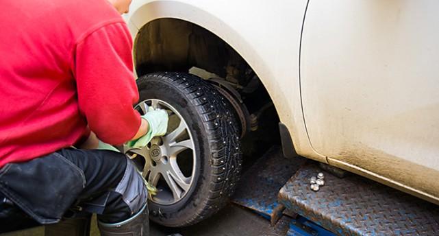 En person byter däck på en bil.