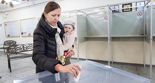En kvinna med en bebis på armen lägger en lapp i en låda av genomskinlig plast.