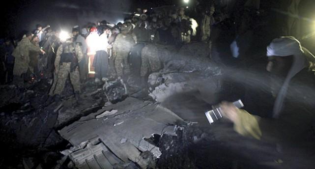 Människor letar överlevande vid vrakdelar av flygplanet. Det är natt och en strålkastare lyser upp platsen.