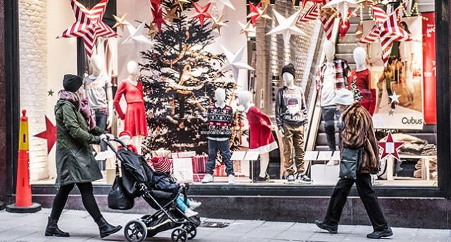 Ett skyltfönster med julgran och andra jul-saker. Människor går förbi framför fönstret.